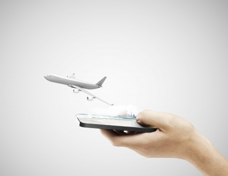 hand holding cellphone and airplane on a gray background