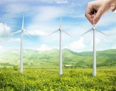 landscape and hand holding eco wind turbine photo