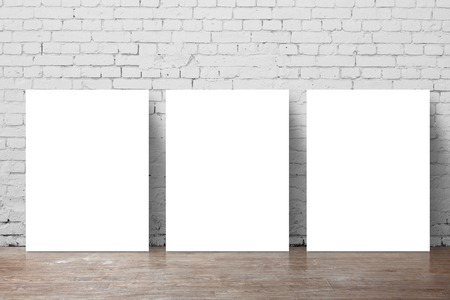 three  poster standing next to a brick wall photo