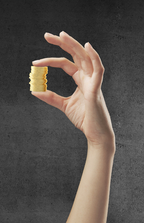 hand holding gold  coins on a concrete background photo