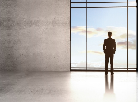businessman thinking in big sunlight office with window