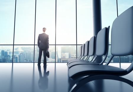 businessman standing in futuristic office with luggage photo