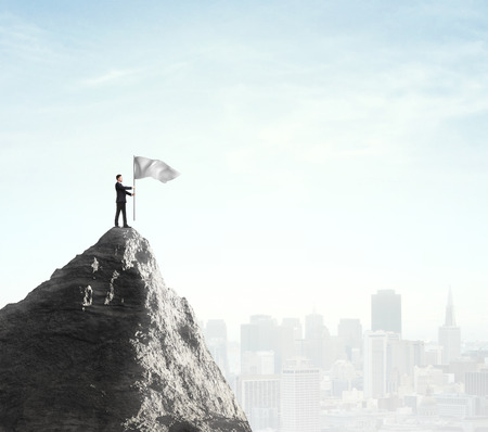 mountain top: businessman standing  with flag on top of mountain