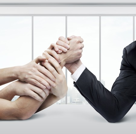 arm wrestling: businessman in opposition with many hands photo