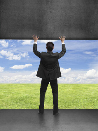 raises: young businessman holding wall in blue field Stock Photo