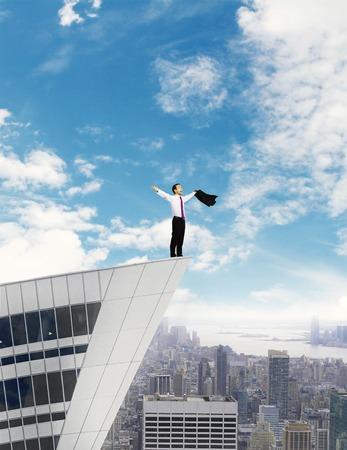 happy businessman standing on building roof on sky background photo