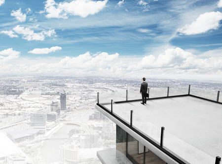 businessman standing on roof of skyscrapper photo