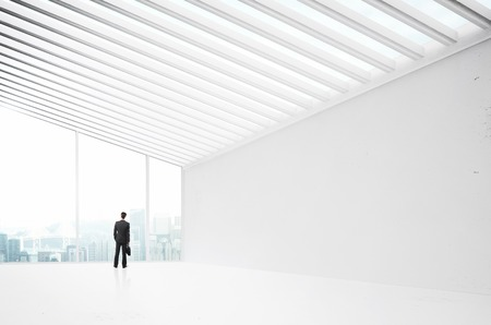 businessman in suit standing in big white office photo