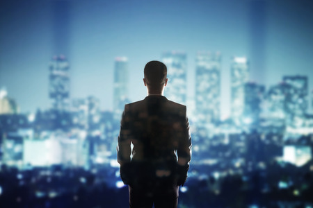 black suit: businessman  in suit looking to night city
