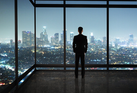 businessman standing in night office Stock Photo