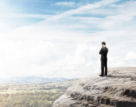 buisnessman thinking on top of mountain photo