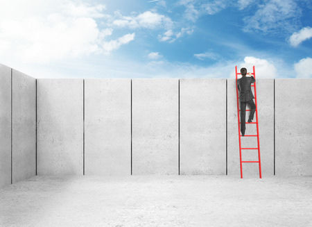 businessman in suit climbing on wall photo