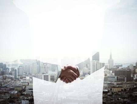 building trust: double exposure handshake businessman on city background Stock Photo
