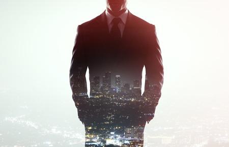 erfolg: Geschäftsmann im Mantel auf einem Stadt-Hintergrund