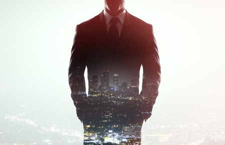 businessman in coat on a city background