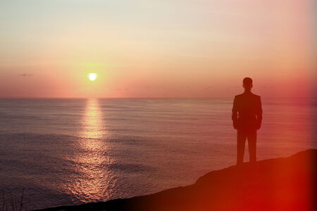 businessman standing on rock and looking to sunrise Stock Photo - 30002549