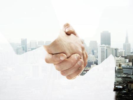 double exposure handshake on a city background