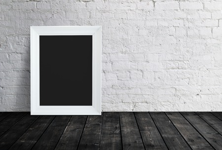 blank black frame hanging on brick wall photo