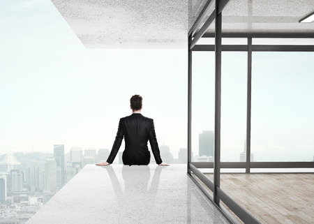 businessman sitting on skyscrapper and looking to city photo