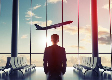 man in airport looking to airplane in sky Banque d'images