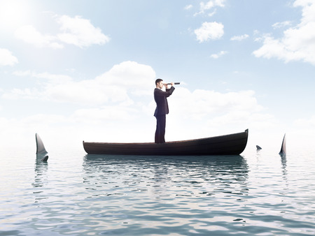 young man looking on boat with sharks around him Stock Photo
