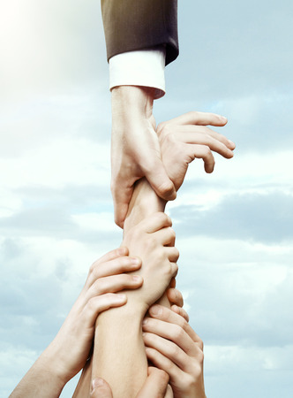 holding close: hand holding hands on a sky background Stock Photo