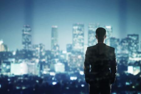 empresario: hombre de negocios en el juego que mira a la ciudad de noche Foto de archivo