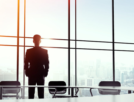 young businessman standing alone in big office photo