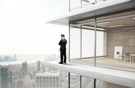 young businessman standing near office and thinking photo