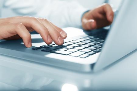 busienssman hands pushing keys of laptop photo