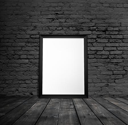blank black frame hanging on brick wall