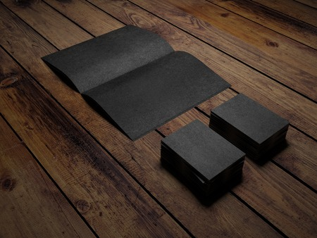 Open black book and paper cards on a wooden table photo