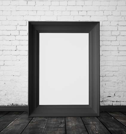 amaged: blank frame hanging on a white brick wall