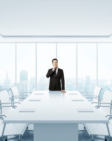 standing businessman: young businessman in suit standing in modern office