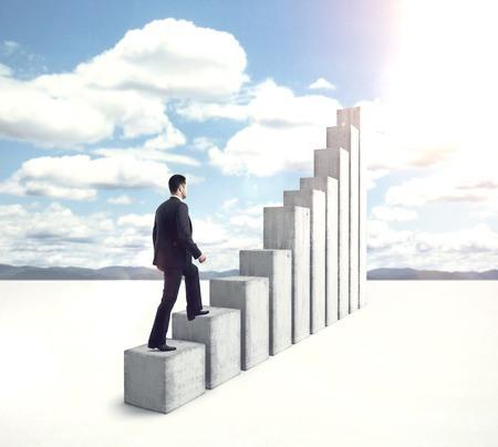 success in business: businessman climbing to stairs on blue background