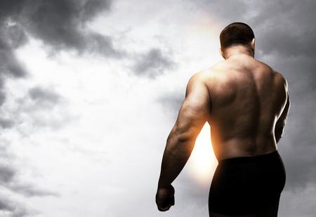 bodybuilding boy: muscular man on a clouds background