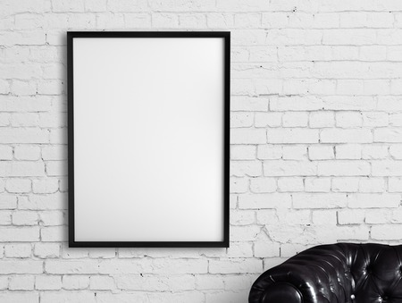 white frame hanging on a brick wall Stock Photo