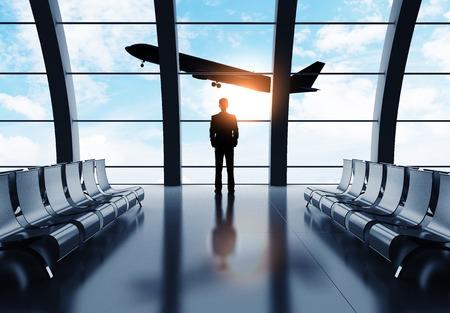man in suit: businessman in airport looking on airplane in sky