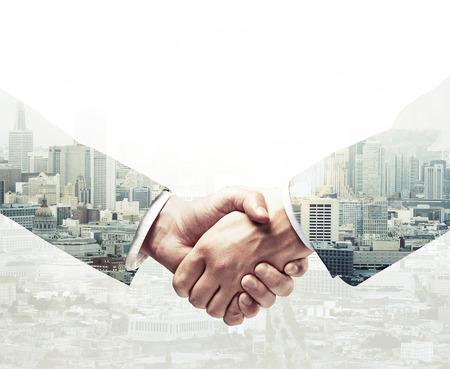 Handshake auf einem Stadthintergrund, Doppelbelichtung