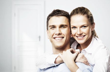 smiling man and woman in white room