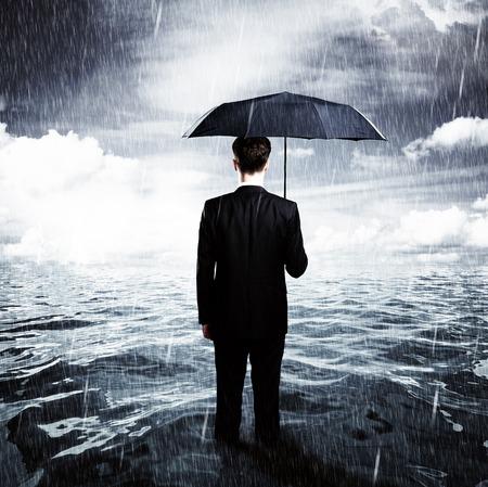man with umbrella standing in ocean business concept