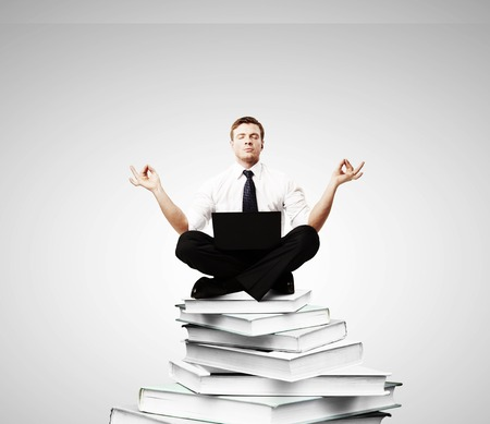 meditation: businessman meditation on a pile of books Stock Photo