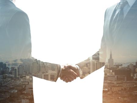 negócio: Dois empresários apertando as mãos no fundo da cidade