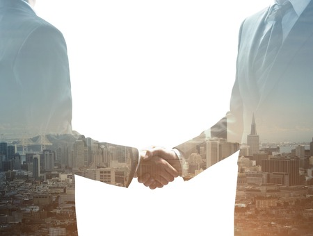 personas saludandose: dos hombres de negocios d�ndose la mano en el fondo de la ciudad Foto de archivo