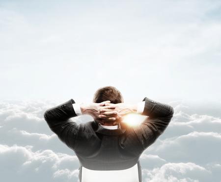 persona sentada: hombre de negocios relajado mirando a las nubes en el cielo