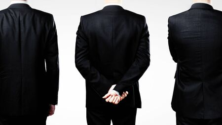 standing businessman: three businessman standing back on a white background