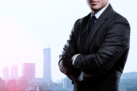 standing businessman: businessman standing and thinking on buildings backgrounds Stock Photo