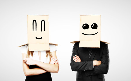 cowardice: businessman and woman with smiling box on head Stock Photo