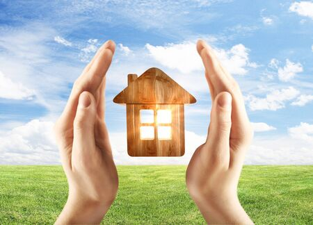 sky and grass: hands holding wooden home on field background