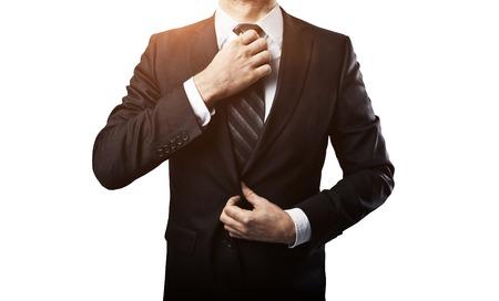 suit: empresario ajusta la corbata en el fondo blanco Foto de archivo